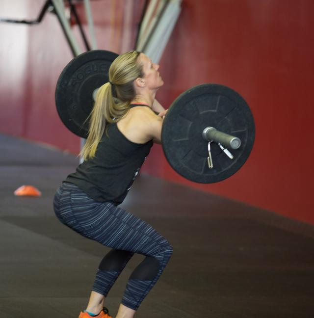 female athlete lifting barbell